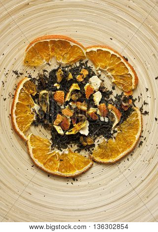 A photo of dried orange slices and tangerine peels on a bamboo plate shot from above with copyspace; 'naturally flavored tea' concept