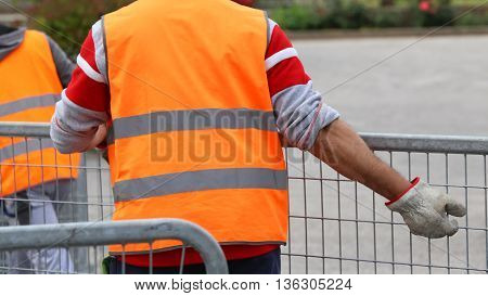 Worker With High Gloves Moves Hurdles Before The Concert Event