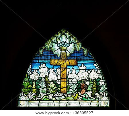 Arched stain glass window in church on black background