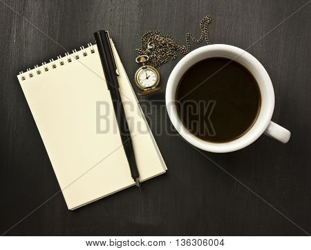 A photo of a cup of black coffee with a vintage chain watch a notepad with copyspace and an ink pen shot from above on a black wooden background texture; 'ideas time' or 'fear of blank page' concept