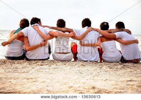 Group of friends hugging at the beach