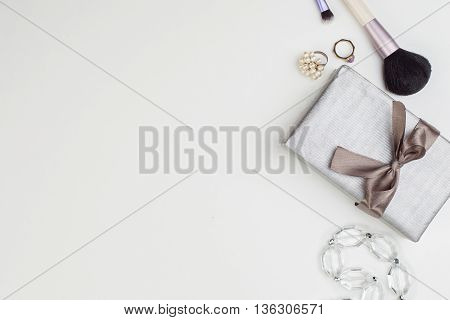 Women's accessories and cosmetics. Top view photo of glamour objects with free space for logo. There are gift and makeup brush
