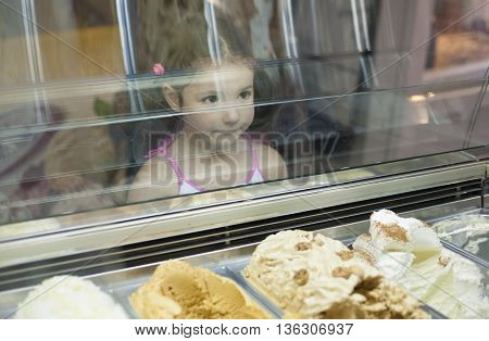Little girl wishes ice cream in pastry shop. Reflections on ice cream counter glasses