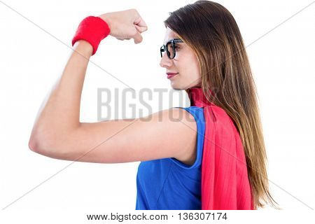 Woman in superhero costume while flexing muscles on white background