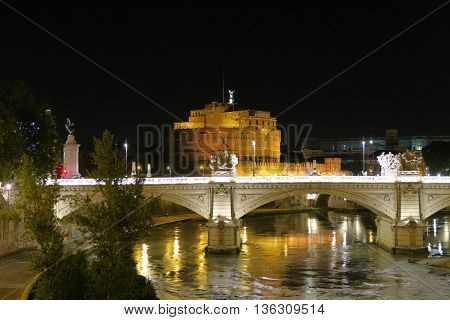 Rome a bridge on Tiber river before Castel Sant'Angelo at night. Ponte Sant'Angelo castle visible in the background at Rome Italy.