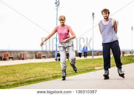 Active young people friends in training suit rollerskating outdoor. Woman and man riding enjoying sport.