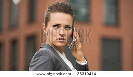 Serious Business Woman Near Office Building Talking Smartphone