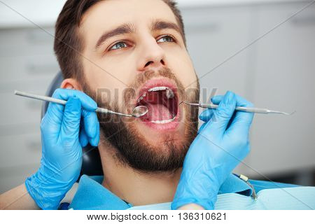 Young Man Getting His Teeth Checked By A Dentist.