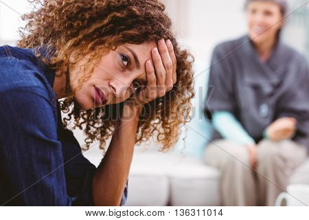 Upset woman with head in hand with mother sitting on background