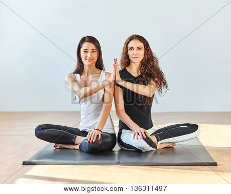 Two Young Women Doing Namaste In Lotus Pose At A Fitness Studio