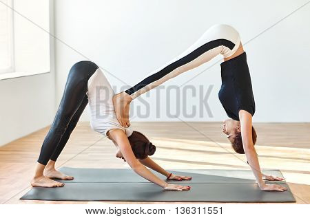 Two Young Women Doing Yoga Asana Double Downward Dog