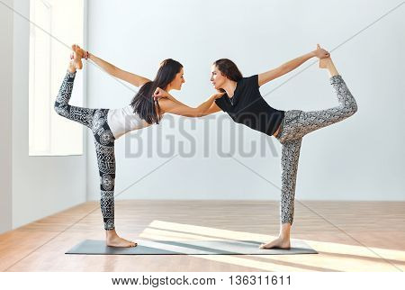 Two Young Women Doing Yoga Asana Lord Of The Dance Pose