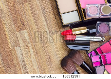 set of brushes, lipsticks, eye shadows with copy space on wooden table desktop