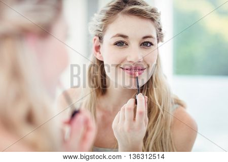 Portrait of smiling young woman applying lip gloss while looking in mirror