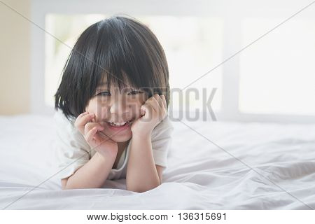 Happy asian baby lying on the bed with copy space on right