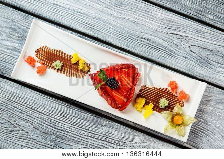 Blackberry on slices of strawberry. Decorated dessert on a plate. Dessert for a gourmet. Strawberry flan cooked at cafe.