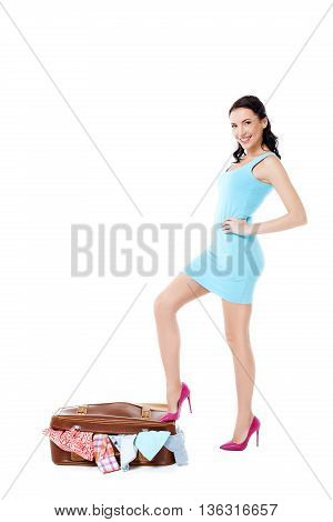 Travel concept. Portrait of stylish beautiful young woman wearing dress and high heels shoes. Isolated on white background. Woman with vintage suitcase full of clothes smiling and looking at camera