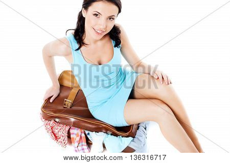 Travel concept. Portrait of stylish beautiful young woman wearing dress and high heels shoes. Isolated on white background. Woman sitting at suitcase full of clothes, smiling and looking at camera