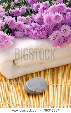 Pink flower on towel with stone on mat