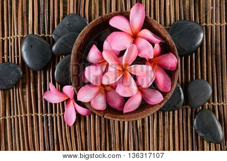 Frangipani in bowl , black stones on mat