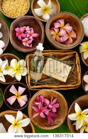 many colorful frangipani and orchid in bowl ,candle on palm leaf
