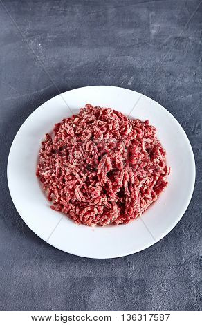 Pinky raw ground beef on a white plate. Ground beef can be used to cook hamburgers, chili con carne or other dishes. Stone cement background