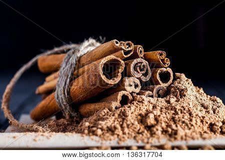 Cinnamon sticks with cinamon powder linked with twine. Black background. Macro image