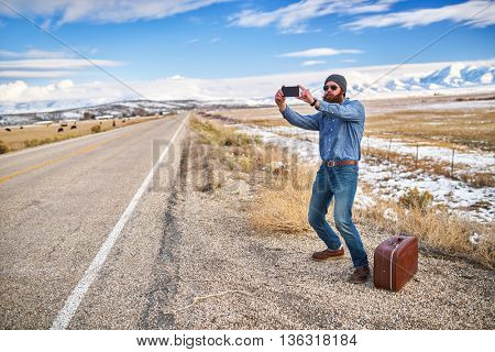 bearded hipster hitch hiker taking selfie beside empty road in nevada