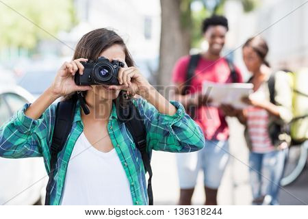 Woman wearing backpack taking photo outdoors
