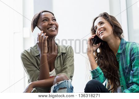 Happy friends talking on a mobile phone