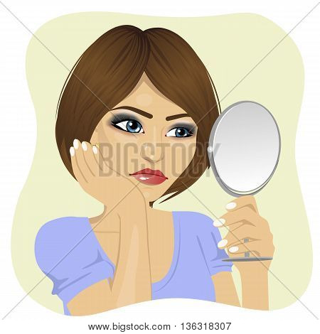 Concerned young woman looking at herself in the mirror