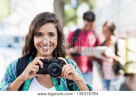 Portrait of young woman holding camera woman smiling