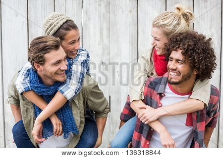 Happy young men giving piggyback to women