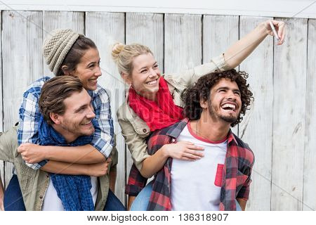 Young woman taking selfie with her friends