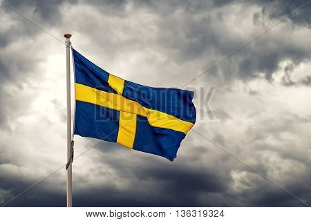 Swedish national flag waving on cold windy day dark stormy clouds in background
