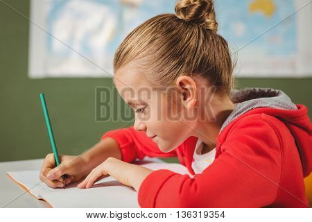 Girl writing in her notebook at school