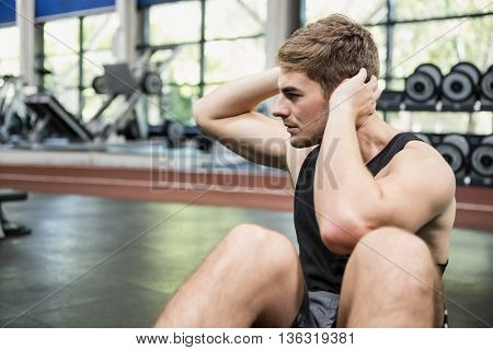Man doing abdominal crunches in gym