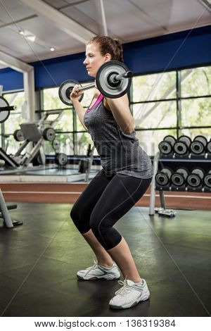 Woman working out with barbell at gym
