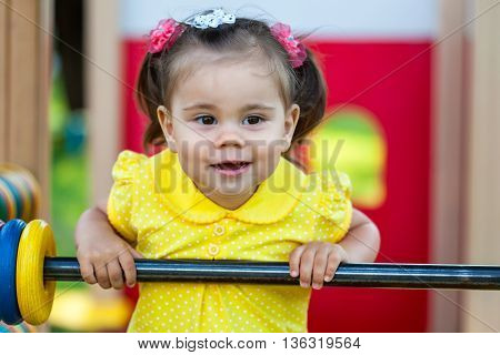 smiling little girl is playing in the park. She has fun on playground