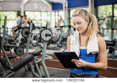 Female gym instructor writing on clipboard in weights room