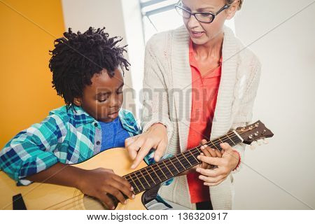 Boy learning how to play the guitar with the help of a teacher