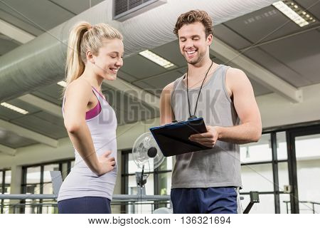 Trainer talking to woman after a workout at gym