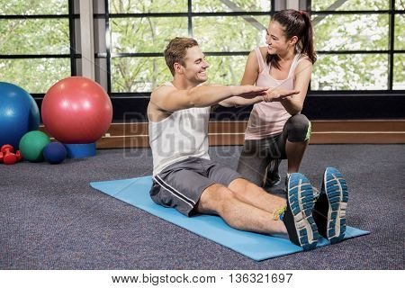 Trainer motivating a man while doing crunches at gym