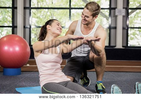 Trainer motivating a woman while doing crunches at gym