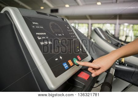 Hand of a person setting control panel of treadmill in gym