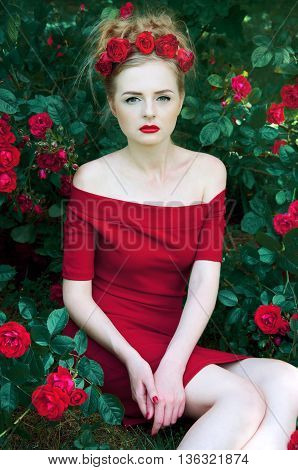 Summer portrait of beautiful blond woman with red roses