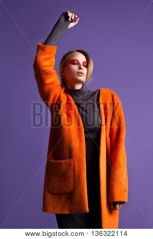 Fashion portrait of beautiful sexy woman model with creative make-up in long coat