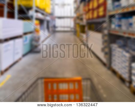 Out of focus aisle in diy warehouse with shopping cart.