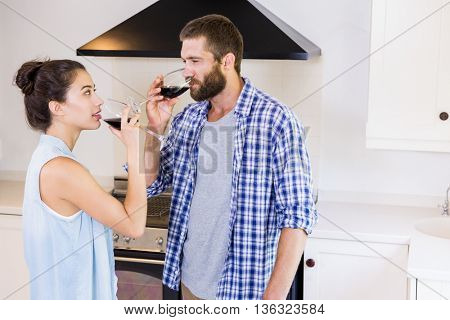 Young couple having red wine in kitchen at home