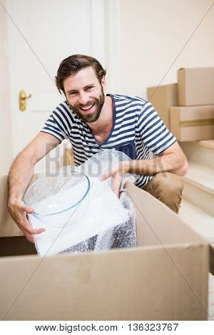 Portrait of young man unpacking carton boxes in his new house